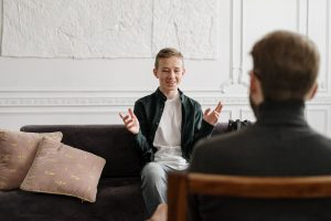 Teenage boy in therapy session with counsellor.