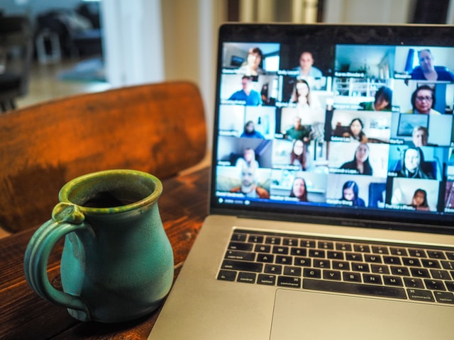 A teal coffee cup on table next to a laptop with Zoom conference on screen.